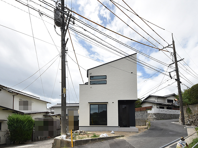 白が基調で黒のサッシ・ドアがアクセントの新築完成写真